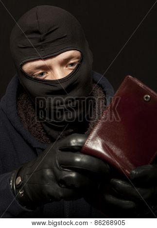 A thief sealing from a brown leather purse