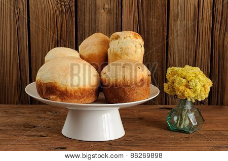Kulich, Russian Easter Yeast Sweet Breads On White Pedestal With Yellow Flowers On Wooden Background