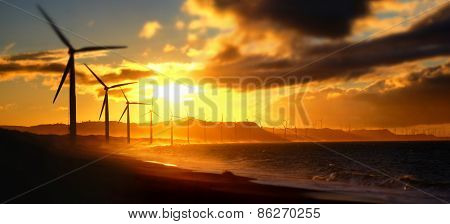 Wind Turbine Power Generators Silhouettes At Ocean Coastline At Sunset. Alternative Renewable Energy