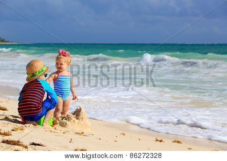 little boy and toddler girl playing on tropical beach