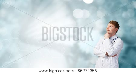 Young thoughtful male doctor on color background looking away