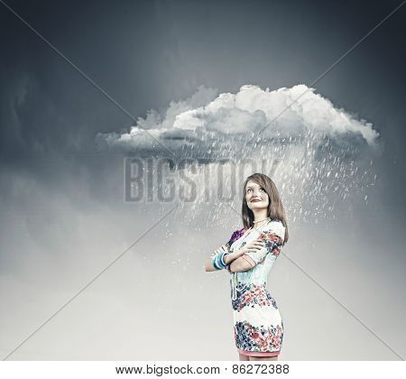 Young pretty woman standing under raining cloud