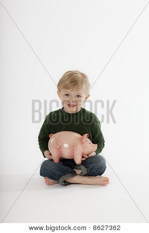 Young Boy Sitting with a Piggy Bank