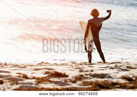 A surfer with his surfboard at the beach doing selfie