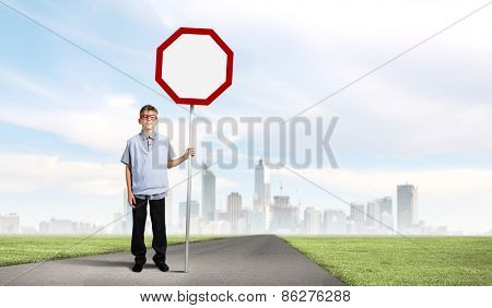 Boy of school age in glasses holding blank road sign