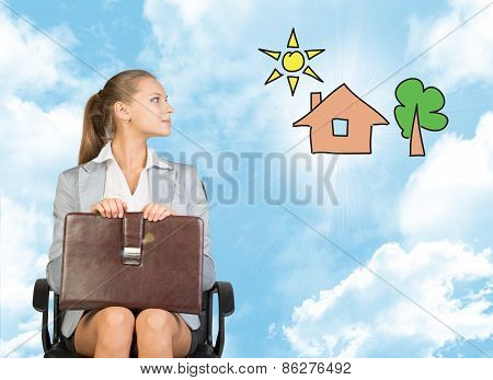 Business woman in skirt, blouse and jacket, sitting on chair imagines house with tree. Against backg