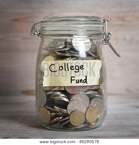 Coins in glass jar with college fund label, financial concept. Vintage wooden background with dramatic light.