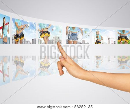 Women in background building construction. Finger presses one of virtual screens