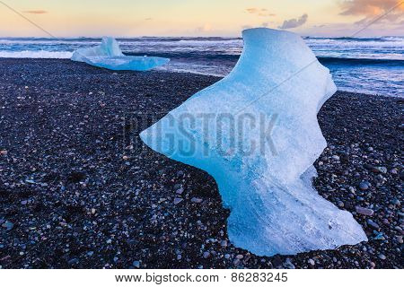 Ice cube on black volcano