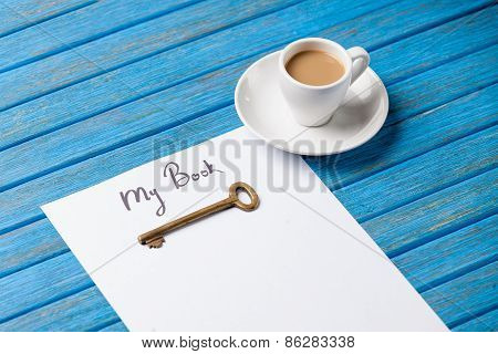 Paper With Inscription And Key Near Cup Of Coffee