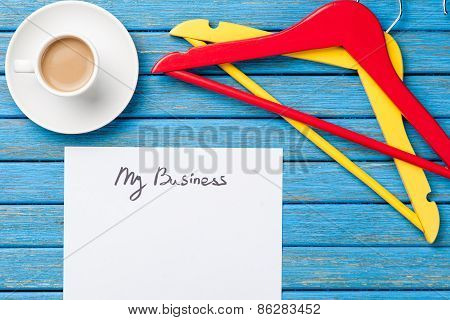 Cup Of Coffee And Inscription On A Paper Near Hangers