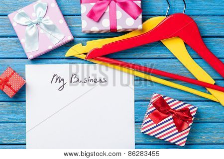 Hangers Near Paper With Inscription And Gifts
