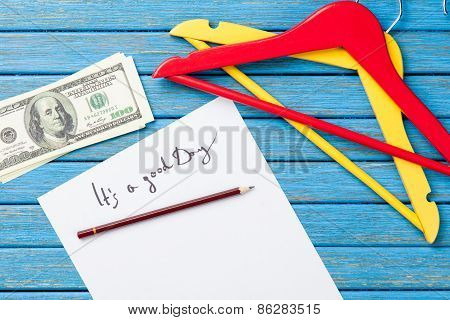 Hangers And Dollars Near Paper With Inscription