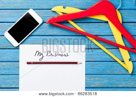Hangers Near Paper With Inscription And Mobile Phone
