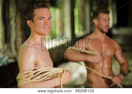 two young men stripped to waist is wrapped rope in his hands in abandoned building focus on left man