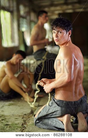 young man in ragged pants looks holds rope in his hands in abandoned building