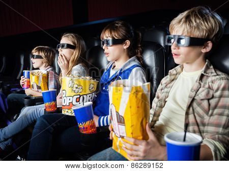 Shocked siblings having snacks while watching 3D movie in cinema theater