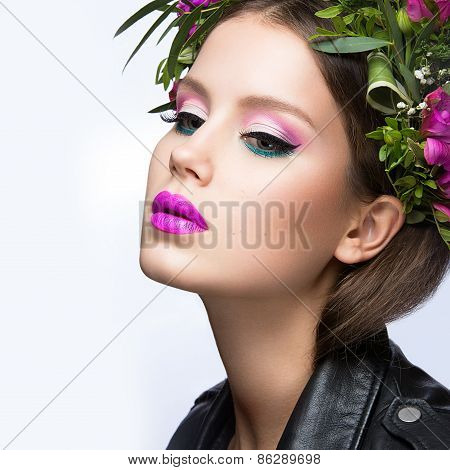Beautiful girl with a lot of flowers in their hair and bright pink make-up. Spring image.