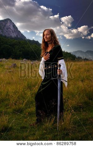 Mystical Woman With A Sword And Historic Dress On A  Mountain Meadow