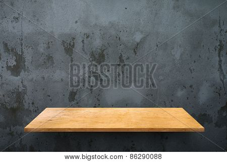 Empty wooden shelf on concrete wall texture
