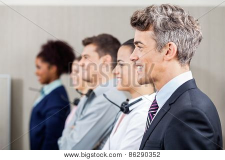 Side view of happy manager standing in row with call center employees at office