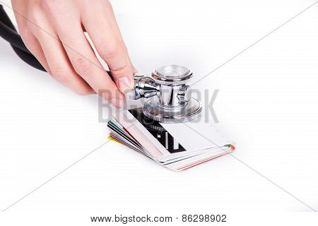Hands Holding Stethoscope On Credit Cards As Symbol Of Money Care And Growth