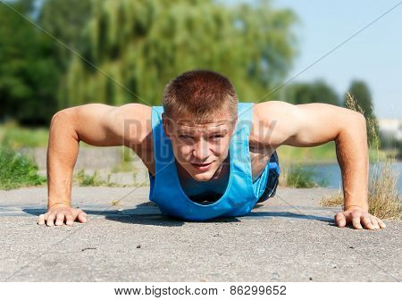 Handsome Young Man In Good Shape Doing Push-up While Outdoor Training
