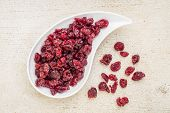 stock photo of teardrop  - dried cranberry on a teardrop shaped bowl against a rustic barn wood - JPG