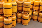 stock photo of cylinder  - bunch of yellow gas cylinder tanks closeup - JPG