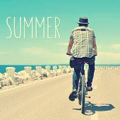 picture of bike path  - the text summer and a back view of an active young caucasian man riding a bike on a no traffic road near the sea - JPG