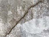 stock photo of fragile  - dangerous deep crack in gray soaked fragile ice on a lake in early spring - JPG
