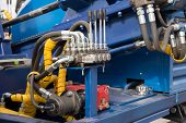 stock photo of hydraulics  - Hydraulic tubes fittings and levers on control panel of lifting mechanism