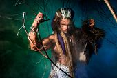 image of werewolf  - Muscular man with dreadlocks and skin through the trees - JPG