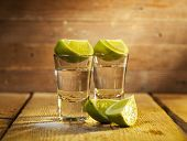 picture of lime  - Set of silver tequila shot with lime fruits on wooden background - JPG