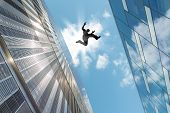 picture of parkour  - Man jumping over building roof against blue sky background
