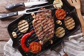 stock photo of grill  - beef steak grilled with onions and eggplant on the grill pan closeup - JPG
