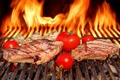 picture of rib eye steak  - Two Rib Steaks Tomato and Mushrooms Roasted Over Flaming BBQ Grill - JPG