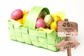 picture of easter candy  - Easter egg hunt sign against speckled colourful easter eggs in a basket - JPG