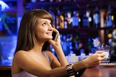 image of handphone  - Young attractive lady at bar talking on phone - JPG