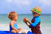pic of infant  - cute infant girl and little boy playing with shells on summer beach - JPG