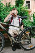 picture of forehead  - tired man with bike wipes his forehead at the park bench - JPG