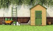 stock photo of wooden door  - Garden with gardening tools and wooden shed with closed door  - JPG
