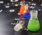 pic of tubes  - Chemistry glass tubes and vessels filled with colorful liquids over the blackboard - JPG