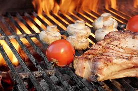 foto of braai  - Rib Steak Tomato and Mushrooms Roasted Over Flaming BBQ Grill - JPG
