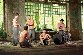stock photo of wet pants  - Five young guys in torn gray pants with rope in his hands in abandoned building  - JPG