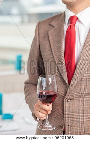 Successful young businessman is drinking alcohol on meeting