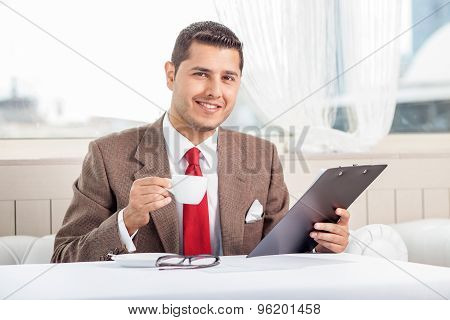 Cheerful young businessman is working on his project