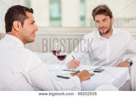 Successful young men has a business lunch in restaurant