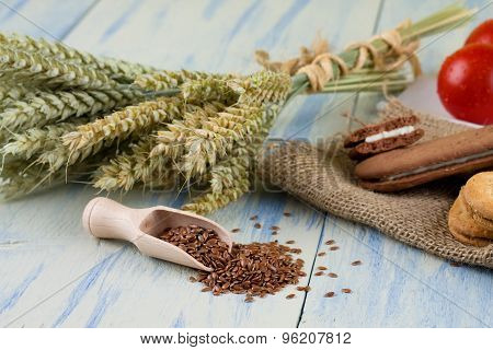 Linseeds On Wooden Spoon In Front Of Grain Ears