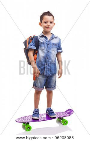 Schoolkid standing with a skateboard and backpack on white background